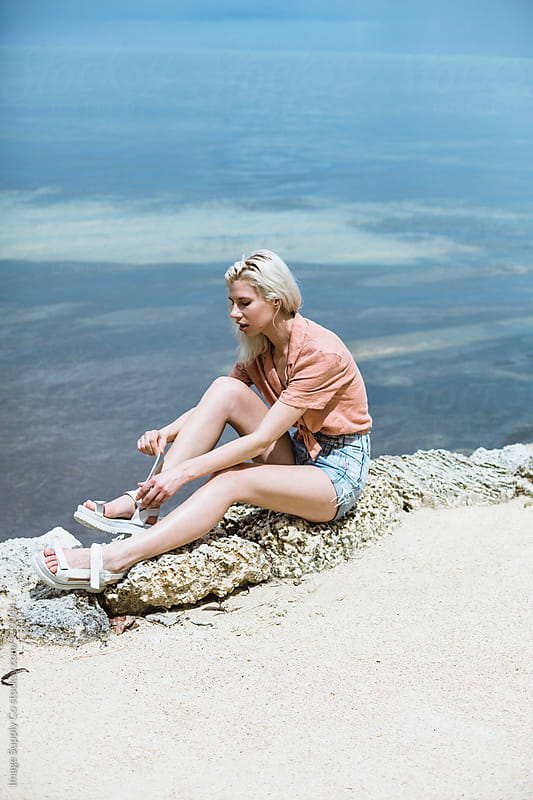 blond girl doing her sandals up waterside by Image Supply Co for Stocksy United