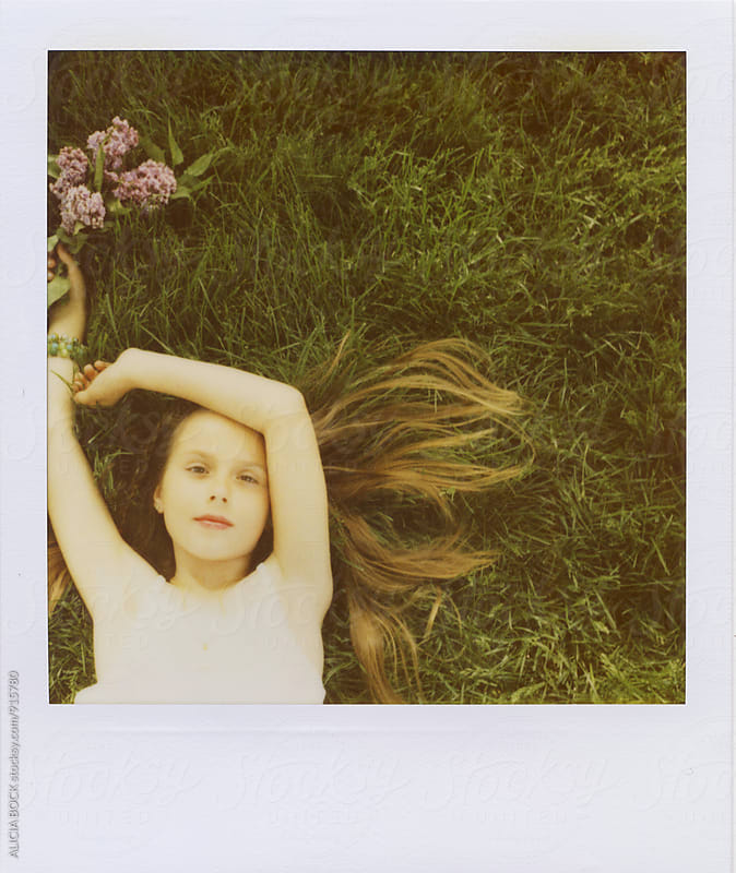 Polaroid Portrait Of A Girl Laying In Green Grass Holding Fresh Lilacs by ALICIA BOCK for Stocksy United