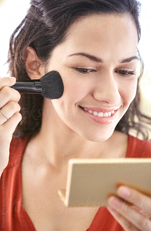 Beautiful Hispanic woman applying makeup.  by Trinette Reed for Stocksy United