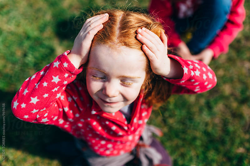 Little Redheaded Girl with Hands on Her Head by VICTOR TORRES for Stocksy United