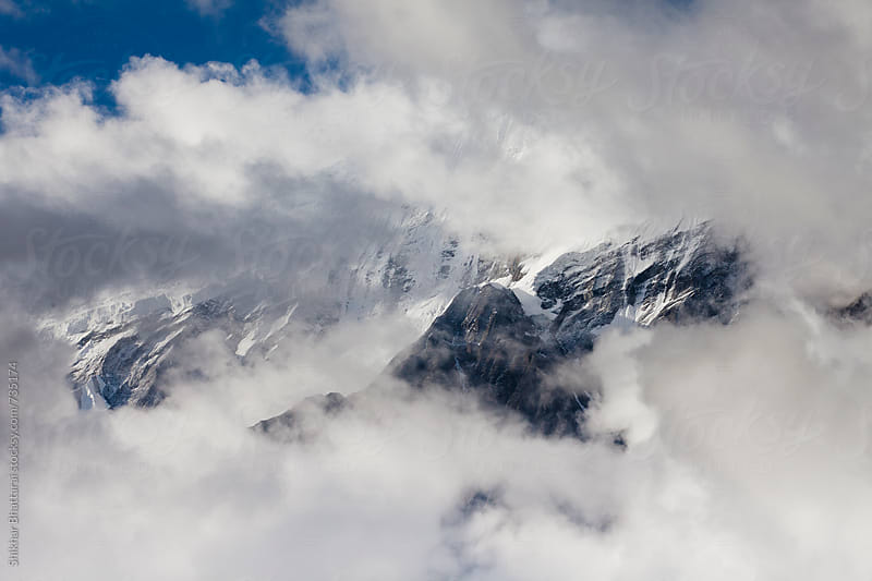 Glimpse of mount Nilgiri through the clouds. by Shikhar Bhattarai for Stocksy United
