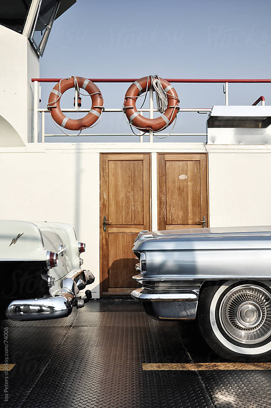 Two vintage cars on a ferryboat by Ina Peters for Stocksy United