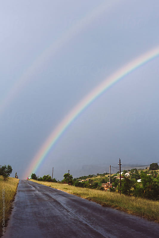 The end of a rainbow hits three figures at the end of a rural road. by Holly Clark for Stocksy United