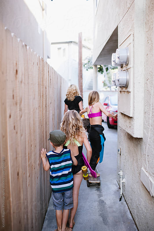 Family leaving home and  walking through an  alley to beach by Kristin Rogers Photography for Stocksy United