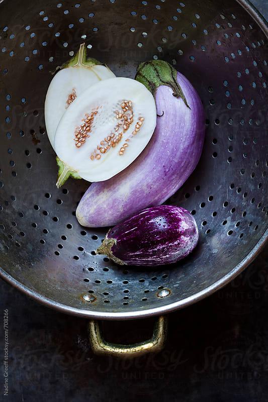 Three varieties of eggplants in colander by Nadine Greeff for Stocksy United
