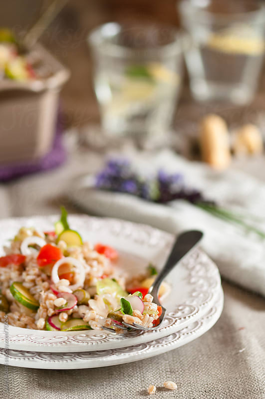spelt salad with fresh vegetables on a white decorated dish by Laura Adani for Stocksy United