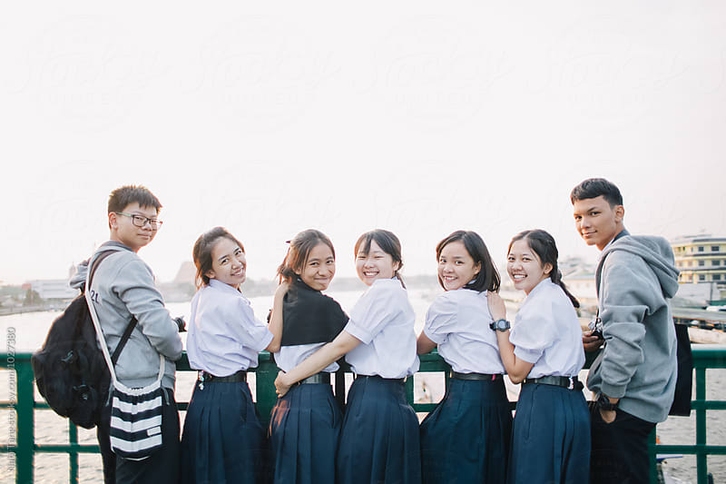 Group of Thai high school student at the bridge over the river at sunset time by Nabi Tang for Stocksy United