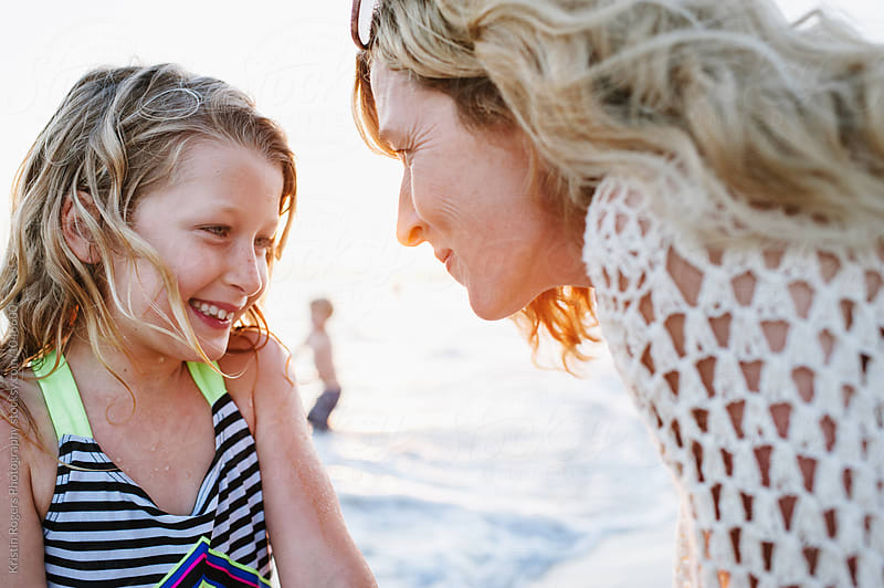 Sweet moment of mom and daughter on the beach by Kristin Rogers Photography for Stocksy United