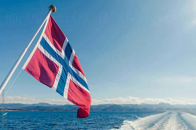 The Norwegian flag with a view from a boat of the ocean and the fjords by Cindy Prins for Stocksy United