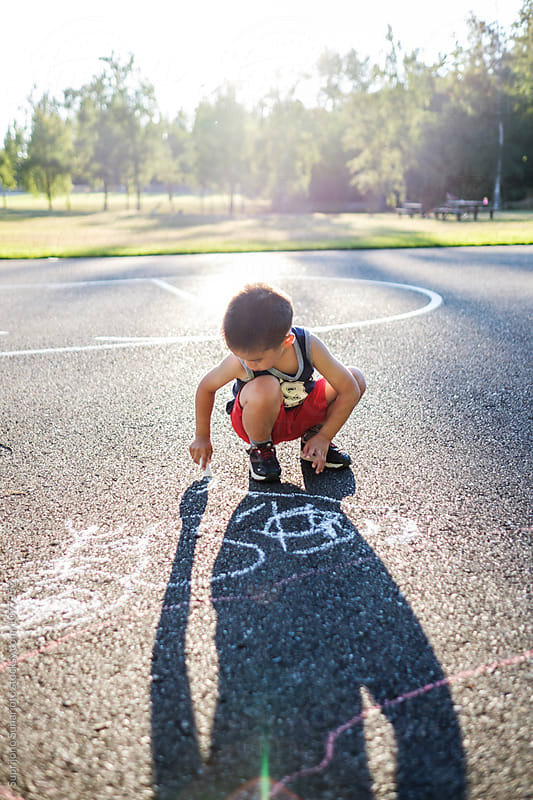 Asian kid drawing with chalk on the ground in the playground by Suprijono Suharjoto for Stocksy United