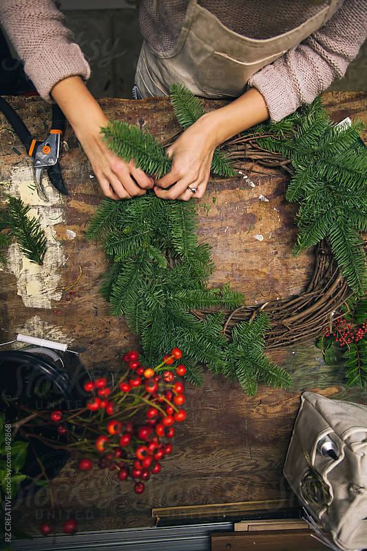 Woman's hands making a holiday wreath in work shop. by Robert Zaleski for Stocksy United