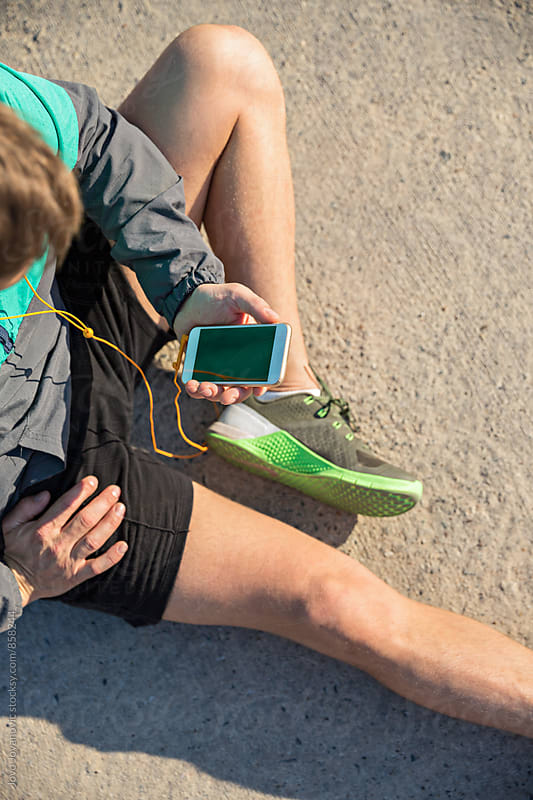 Aerial view of a fit man stretching on the ground and looking at his smartphone  by Jovo Jovanovic for Stocksy United