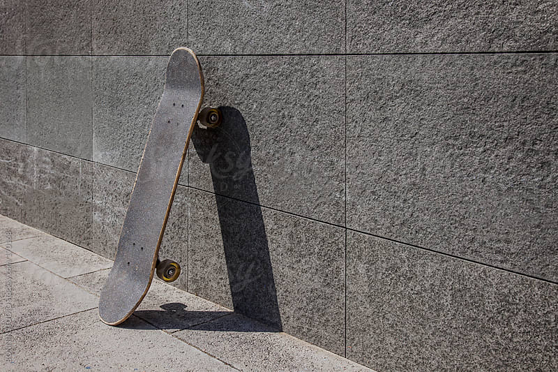 Skateboard supported on grey wall. by BONNINSTUDIO for Stocksy United