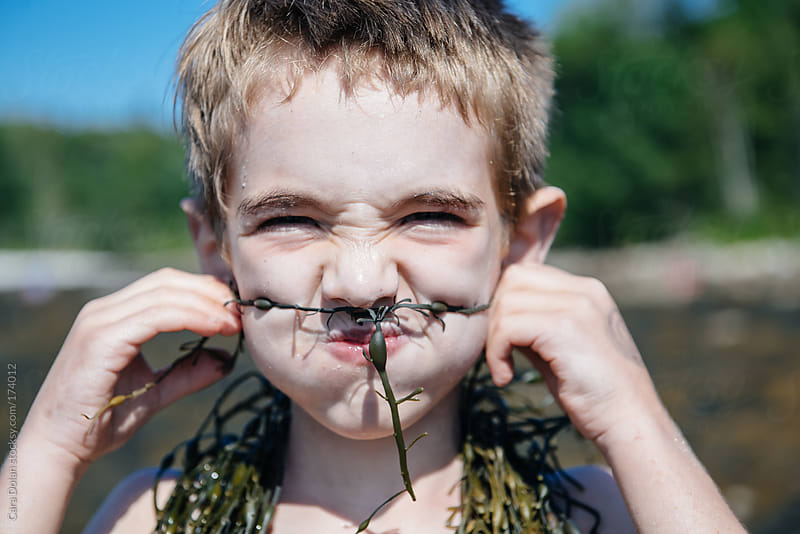 Silly boy makes a mustache out of seaweed by Cara Dolan for Stocksy United