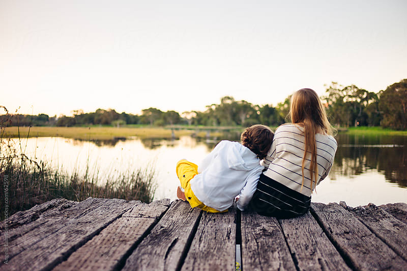 Boy and girl sitting on a dock over a lake by Angela Lumsden for Stocksy United