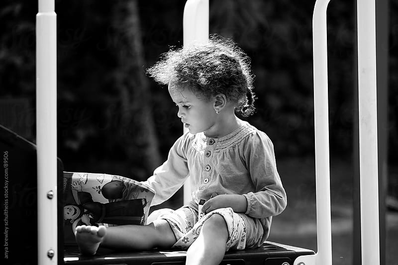 Portrait of young child coloring intently at a park by anya brewley schultheiss for Stocksy United