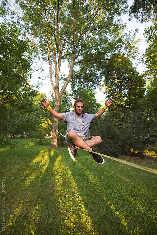 Young man sitting in lotus pose on a slackline by RG&B Images for Stocksy United