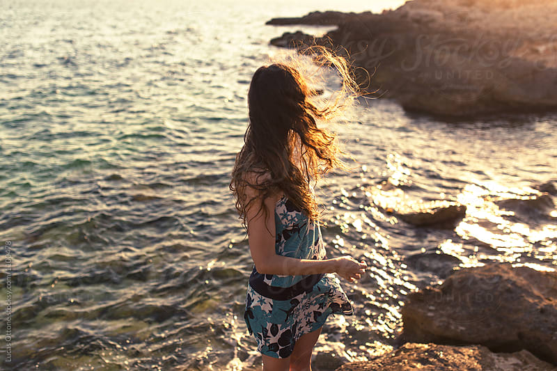 Woman shaking her hair on a sunset in front of the sea by Lucas Ottone for Stocksy United