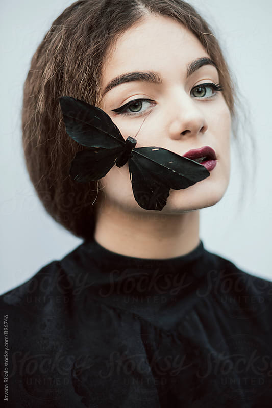 Portrait of a young woman and black butterflies by Jovana Rikalo for Stocksy United
