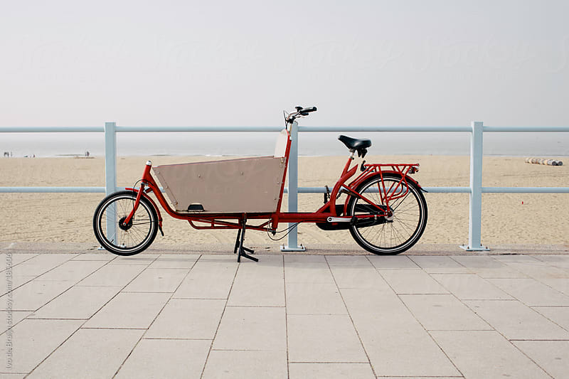 Classic red tricycle or bike on the boulevard with the beach and sea on the background by Ivo de Bruijn for Stocksy United