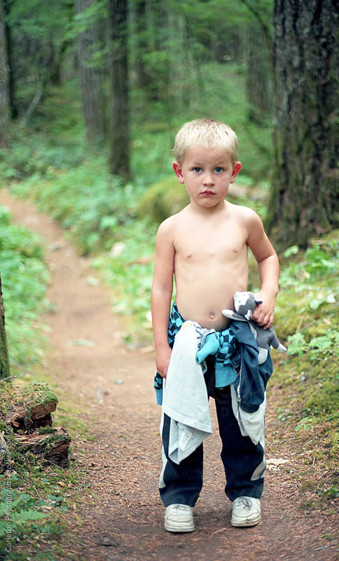 Shirtless boy holding stuffed wolf stands on trail in the woods by Carleton Photography for Stocksy United