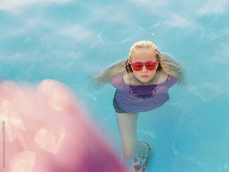 colorful pool fun with girl and sunglasses by wendy laurel for Stocksy United