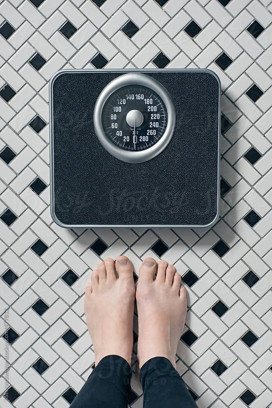 Woman standing in front of bathroom scale on tiled floor by Kathryn Swayze for Stocksy United