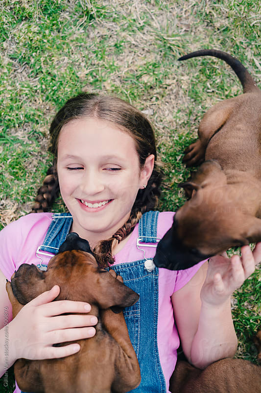 girl on grass with puppies by Gillian Vann for Stocksy United