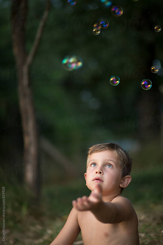 Boy catch bubbles. by Dejan Ristovski for Stocksy United
