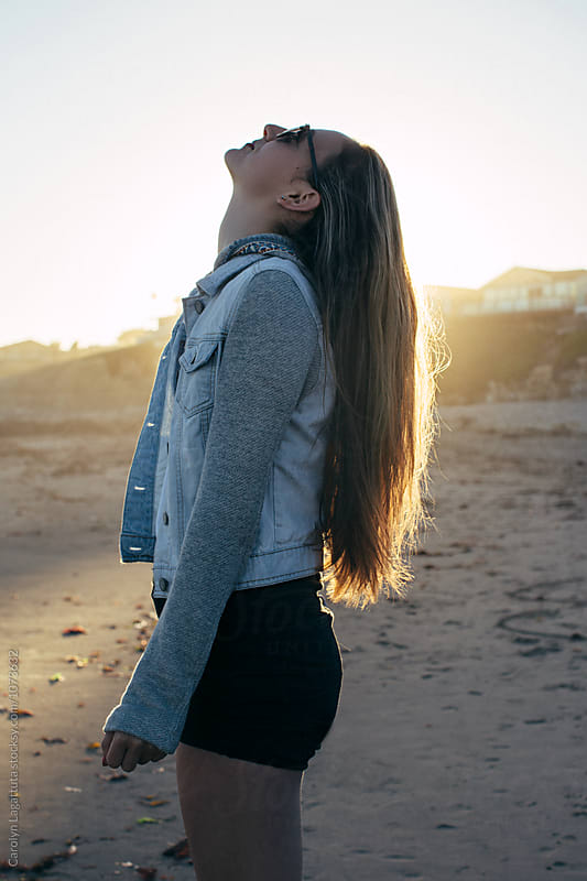 Teenage girl at the beach with the sunlight in her hair by Carolyn Lagattuta for Stocksy United