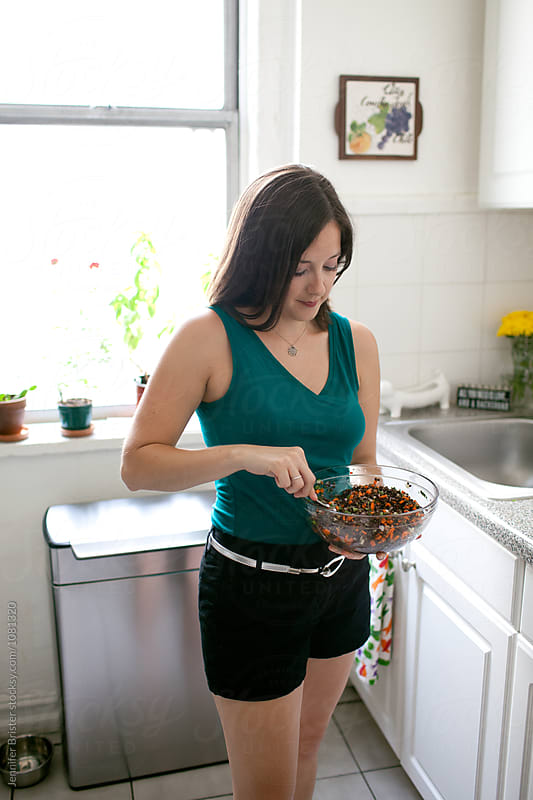 Woman stirs salad by Jennifer Brister for Stocksy United