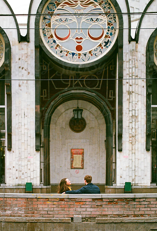 A pair sitting near big building by Danil Nevsky for Stocksy United