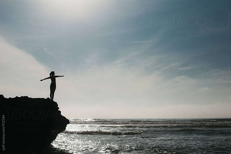 Woman feeling uplifted and empowered on a rock above the ocean by paff for Stocksy United