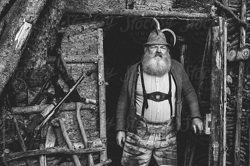 old bearded man in typical austrian lederhosen looking out of a wooden cabin by Leander Nardin for Stocksy United