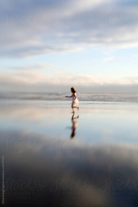 Girl running on beach with full body reflection showing below her in ocean - soft focus image creating dreamy effect by Dina Giangregorio for Stocksy United
