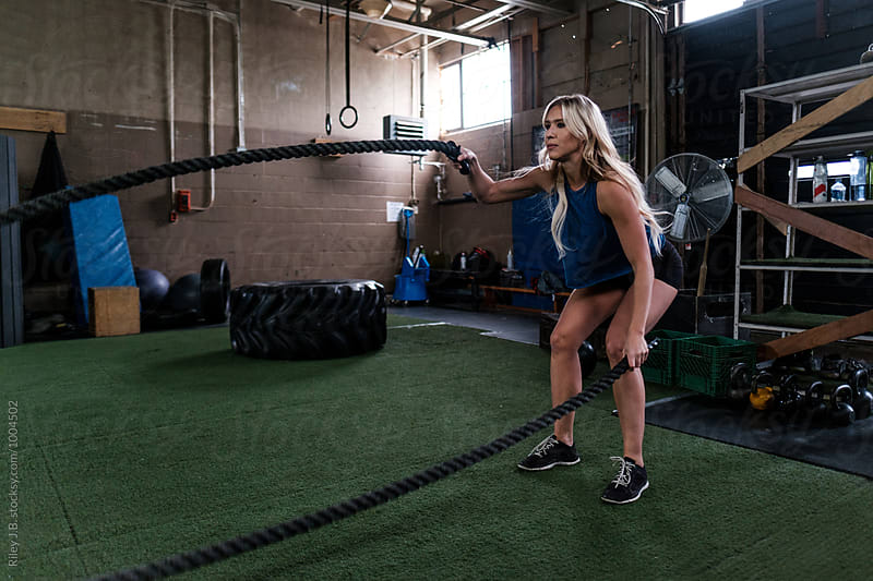 An attractive woman using battling ropes in gritty gym by Riley J.B. for Stocksy United