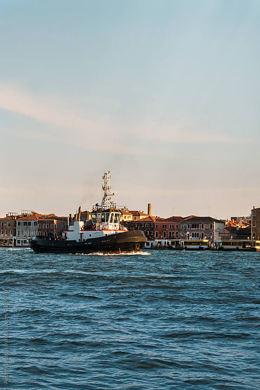 Small fishing ship getting in port with city in background.Italy by Marko Milanovic for Stocksy United