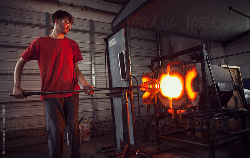 Glass: Man Uses Furnace to Reheat Glass Before Shaping by Sean Locke for Stocksy United