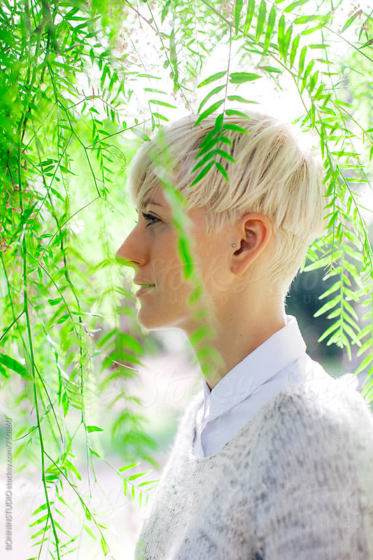 Side view of a blonde woman standing between green leaves. by BONNINSTUDIO for Stocksy United