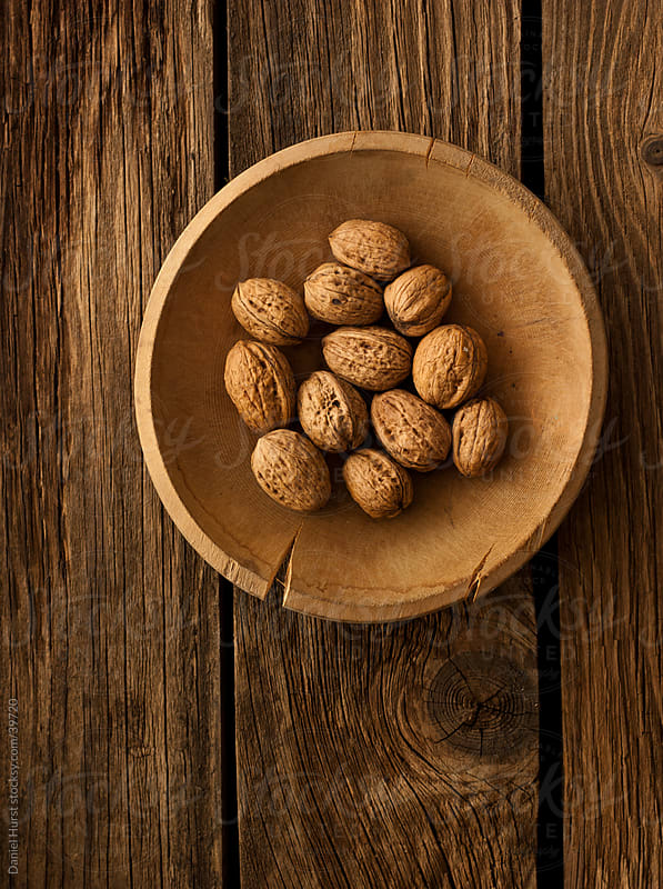 Bowl of walnuts on wooden texture by Daniel Hurst for Stocksy United