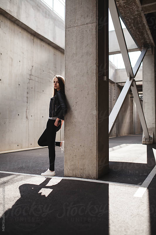 Beautiful girl standing on a concrete background by MEM Studio for Stocksy United