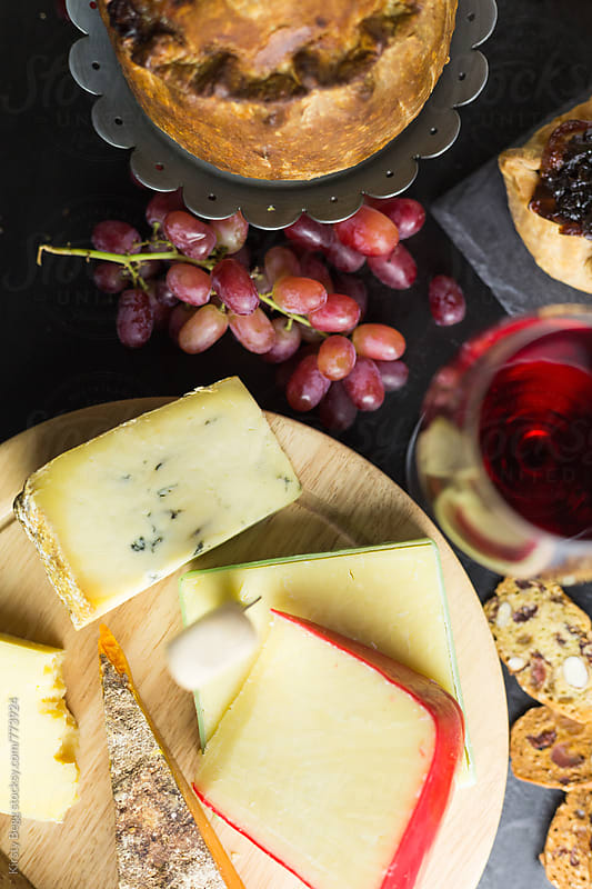 Cheese board with grapes and pork pies by Kirsty Begg for Stocksy United