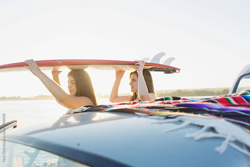 teens lift surfboard off roof of car by Tana Teel for Stocksy United