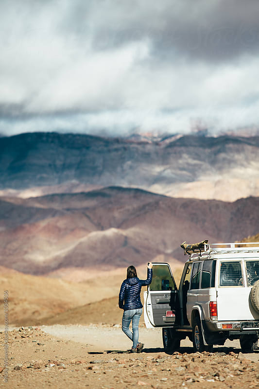 Woman on a roadtrip through scenic mountainous desert by Micky Wiswedel for Stocksy United
