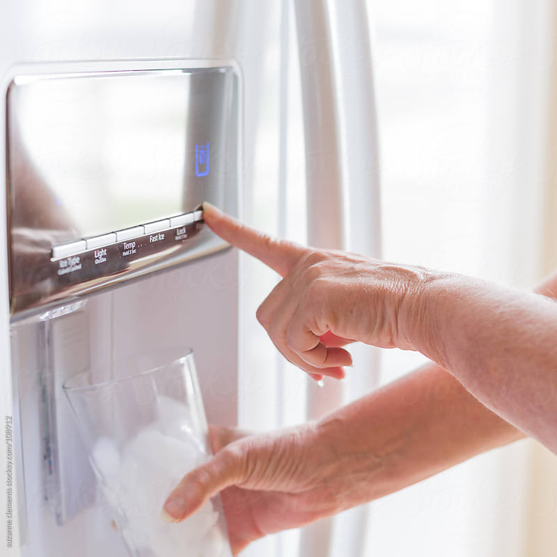 Woman Dispenses Filtered Water from Her Fridge  by suzanne clements for Stocksy United