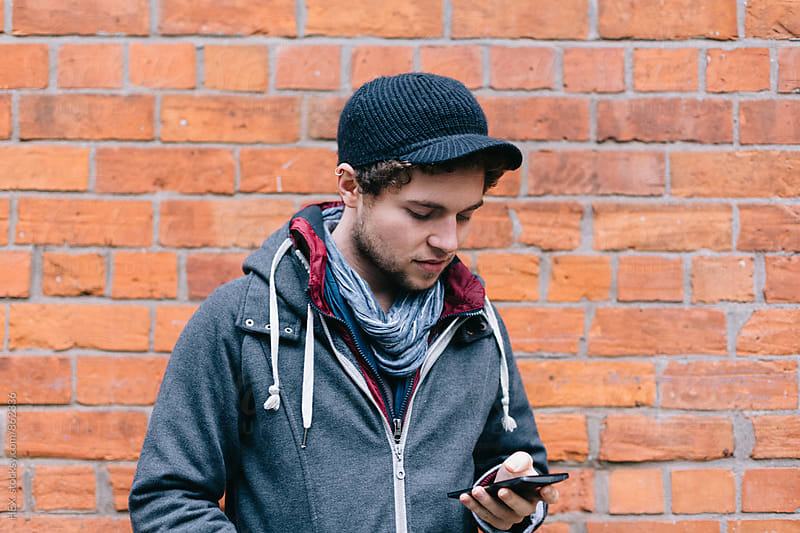 Young Guy Using a Mobile Phone by HEX. for Stocksy United
