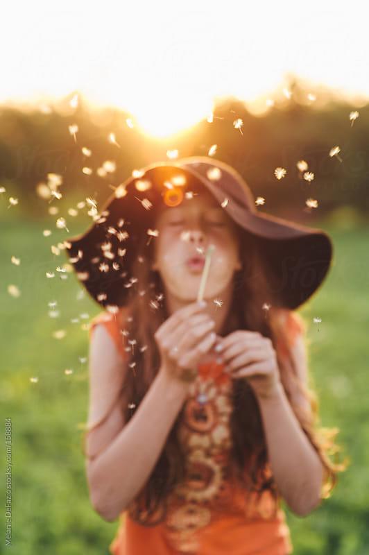 Blowing dandelions by Melanie DeFazio for Stocksy United