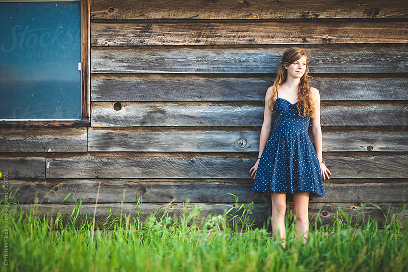 Young girl leaning against an old barn looking into the sunset by Christian Tisdale for Stocksy United