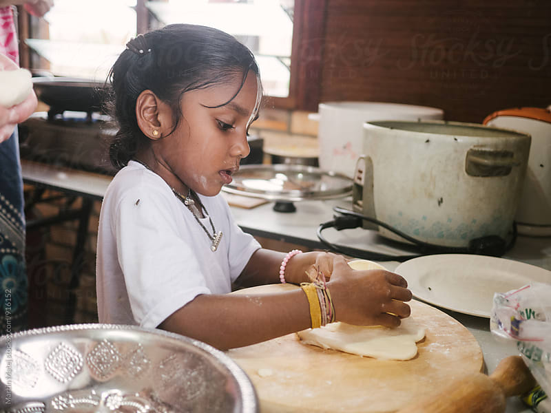 Tiny indian girl helps in kitchen with dough by Martin Matej for Stocksy United