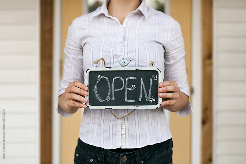 Shop: Owner Holding Open Sign By Front Door by Sean Locke for Stocksy United